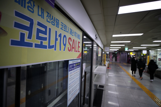 A notice posted on a store Sunday in the underground shopping area in Myeong-dong, central Seoul, advertises a sale and makes a plea for a rent cut. [YONHAP]