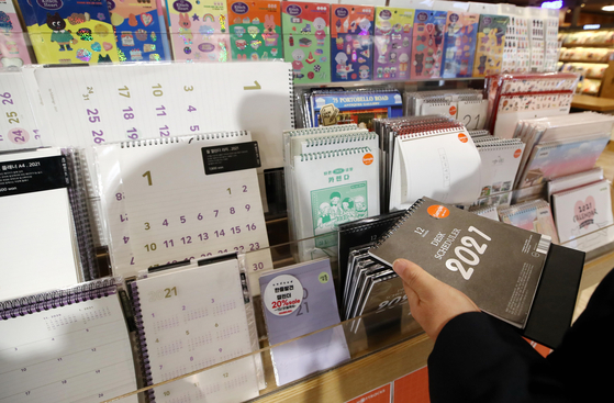 A customer looks at calendars in a bookstore in Seoul on Tuesday. Next year will have two fewer days of rest — weekends and national holidays — than this year and four days fewer than 2019. [YONHAP]