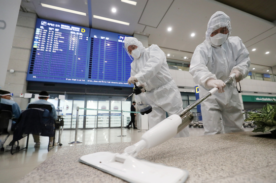 Officials disinfect Incheon International Airport on Monday as health authorities announced Korea's first detection of a highly transmissible coronavirus variant now sweeping Britain. [NEWS1]