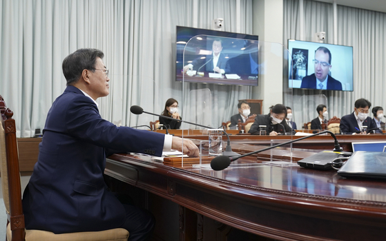 President Moon Jae-in, left, participates in a videoconference with Moderna CEO Stéphane Bancel on Monday at the Blue House.  [YONHAP]