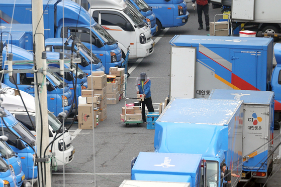 A delivery man from CJ Logistics loads packages into a truck at a terminal in Seoul in October. [YONHAP]