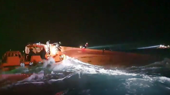 Marine police attempt to rescue seven fishermen after their boat capsized in the waters off Jeju Island on Tuesday night. None of the fishermen have been rescued as of noon Wednesday. [NEWS1]