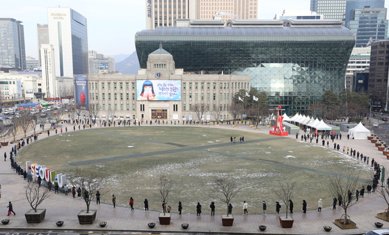 People line up at a Covid-19 testing site near Seoul City Hall in Jung District, central Seoul, on Dec. 17 as daily new infections remain above 1,000 across the nation. [NEWS1]