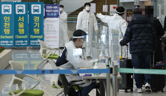 Visitors from Osaka, Japan, are guided towards buses headed to Covid-19 testing sites Wednesday at Incheon International Airport, as health authorities announced Korea detected two new cases of the new coronavirus variant spreading through Britain. [YONHAP]