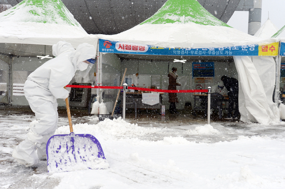 A health official clears snow at a Covid-19 testing site in Gwangju Wednesday morning as the city saw some 14 centimeters (5.5 inches) of snow. [NEWS1]