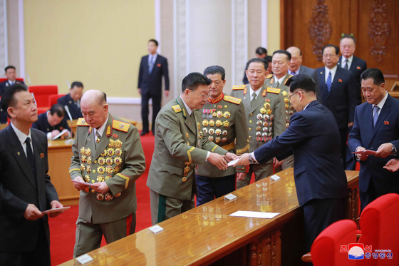 Delegates of the North's ruling Workers' Party receive certifications for their participation in the upcoming eighth Party Congress to be held early next month, as shown in a state media photograph. Representatives from across the country have already gathered in Pyongyang for the event. [YONHAP]