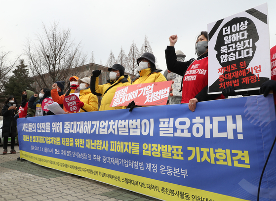 A group of people stage a protest to advocate the passage of a bill aimed at toughening penalties for industrial accidents on Monday at the National Assembly in Yeouido, western Seoul. [YONHAP]