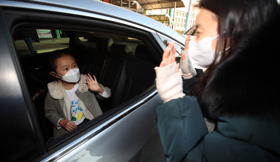 A first grader at Jeongpyeong Elementary School in Gyeongsan, North Gyeongsang, meets her teacher for the first time Monday during a drive-thru orientation organized by the school to prevent the spread of the coronavirus. [YONHAP]