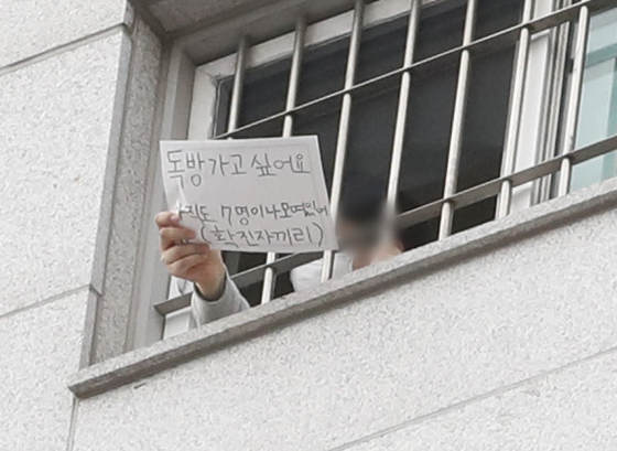 """An inmate at Seoul Dongbu Detention Center in Songpa District, southern Seoul, holds a sign Sunday that reads, """"I want a room to myself. Seven confirmed patients are still gathered [in a single room]."""" More than 1,100 coronavirus cases have been traced to the facility. [NEWS1]"""