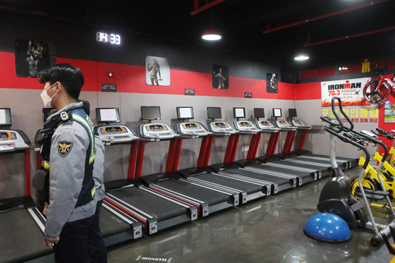 A police officer looks around a gym in Pocheon, Gyeonggi, Monday, to check for any violations of social distancing rules after the gym owner opened his business in defiance of the government's shutdown orders on all indoor sports facilities in the greater Seoul area. [YONHAP]