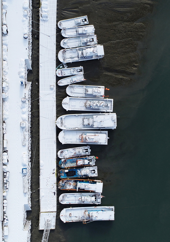 Fishing boats covered with snow are moored at Seoldo Port in Yeonggwang County, South Jeolla, on Wednesday morning. [YONHAP]