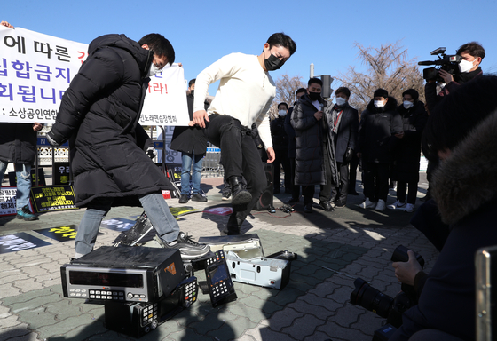 In front of the National Assembly on Wednesday, owners of coin noraebang, or booth-type singing rooms, stage a press event at which they destroy singing room equipment to protest the government's social distancing measures. They pledged they will not obey any shutdown order after Jan. 18. [NEWS1]