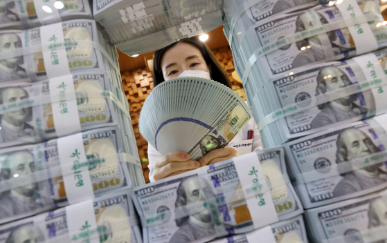 An employee of Hana Bank organizes dollars at its headquarters in Jung District, central Seoul, on Wednesday. [YONHAP]