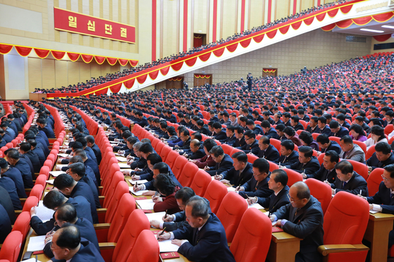Delegates and participants of the 8th Party Congress jot down notes as Kim delivers his address at the event. Several thousand were packed into the auditorium for the congress, though not one wore a mask. [NEWS1]
