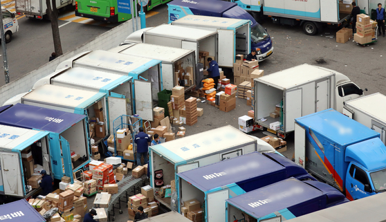 Delivery workers load packages onto a truck at a terminal in Seoul on Nov. 13. [NEWS1]