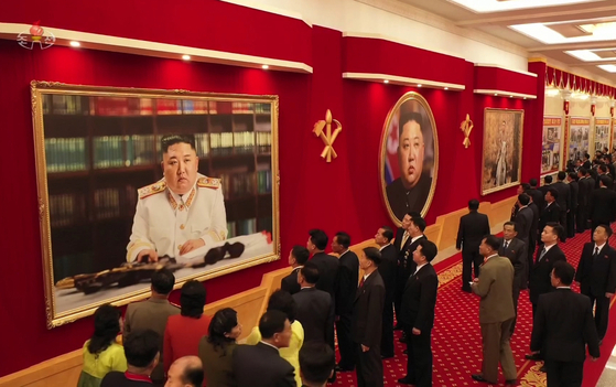 Delegates attending the 8th Congress of the Workers' Party in Pyongyang admire Kim Jong-un's portrait in marshal regalia, as shown in this state media photograph. [YONHAP]