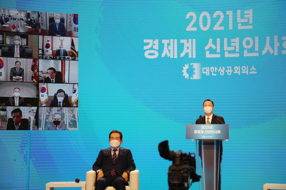 Park Yong-maan, Korea Chamber of Commerce & Industry chairman, right, speaks during the business community's New Year's event held at the business group's headquarters in central Seoul on Thursday with Prime Minister Chung Sye-kyun, left, attending. [YONHAP]