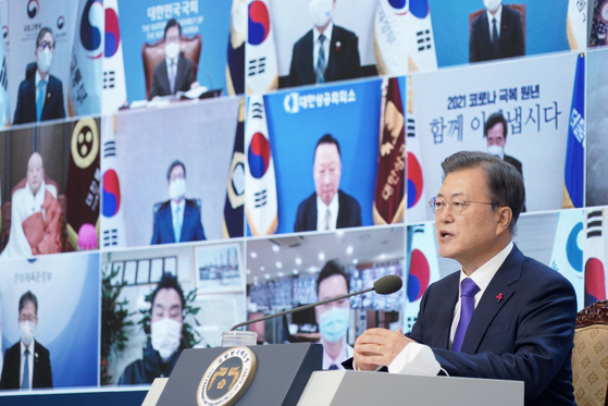 """President Moon Jae-in speaks during a New Year's meeting with business and social leaders held via videoconference in the Blue House on Thursday. President Moon stressed the importance of national unity in 2021, saying the Covid-19 crisis has reminded the people that they are """"connected"""" to one another. The president described 2021 as the year of """"recovery"""" from the Covid-19 crisis. [NEWS1]"""