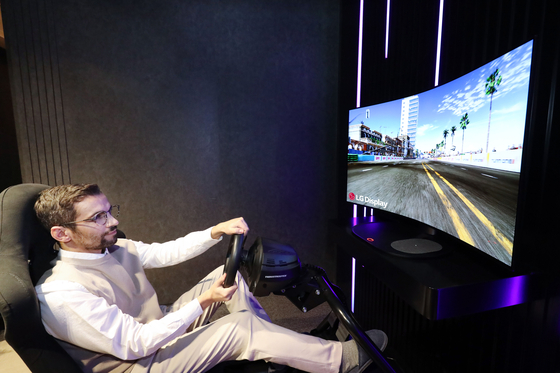 A model enjoys a game with LG Electronics' new 48-inch bendable OLED. [LG Electronics]
