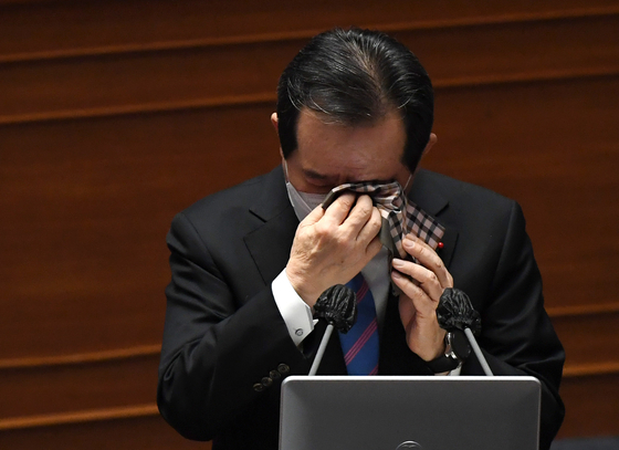 Prime Minister Chung wipes his tears after responding to a question about small business owners' crisis in the Covid-19 pandemic in Korea at a session at the National Assembly in Seoul on Friday. [YONHAP]
