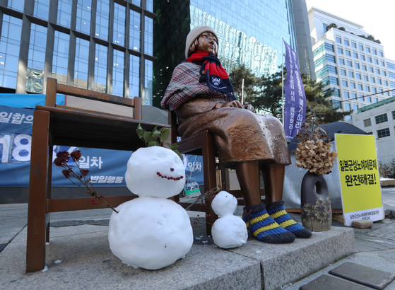 A statue representing comfort women victims near the former Japanese embassy in central Seoul is bundled up for the cold weather, as a local court made a landmark ruling Friday that the Japanese government is responsible for paying damages to victims of its wartime sexual slavery. [YONHAP]