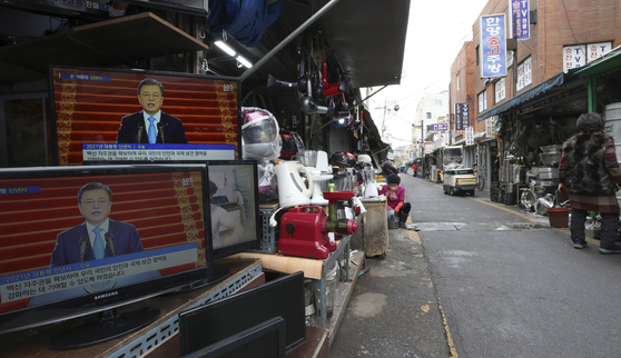 Television sets at a thrift shop in Jungang Market in Jung District, central Seoul, show President Moon Jae-in delivering a New Year address Monday. [YONHAP]