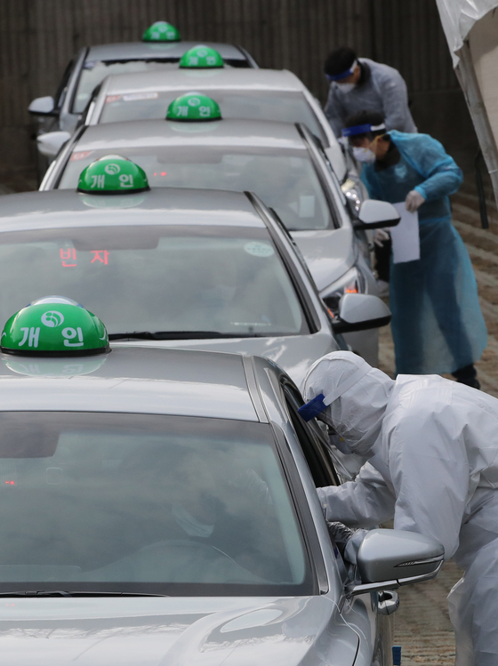 Medical workers extract samples from taxi drivers at a drive-thru testing site in Asiad Main Stadium in Busan on Monday, in a pre-emptive measure to detect Covid-19 infections among taxi drivers. [SONG BONG-GEUN]