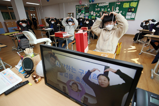 Sixth graders of the Jungheung Elementary School in Gwangju attend an 'untact' graduation ceremony on Tuesday while their parents participate by videoconference to observe the ceremony. [NEWS1]