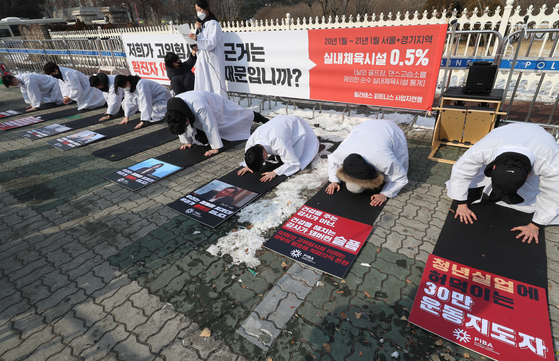 Representatives of a federation of Pilates and fitness center owners take a deep bow as they urge the government Tuesday in front of the National Assembly in Yeouido, western Seoul, to allow them to reopen their businesses. [YONHAP]