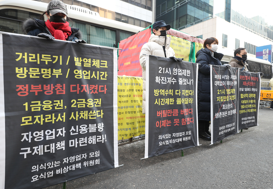 Members of an emergency committee representing restaurant owners stage a protest in front of the ruling Democratic Party's headquarters in Yeouido, western Seoul, on Tuesday, urging them to lift the regulation that forces restaurants to close at 9 p.m. [YONHAP]