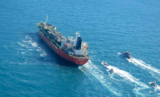 MT Hankuk Chemi, a South Korean-flagged oil tanker, is escorted by Islamic Revolutionary Guard vessels Monday to Iranian waters after being seized by Iranian authorities in the Strait of Hormuz in a photo released by the Tasnim News Agency. [AFP/YONHAP]