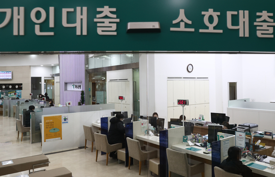 Customers speak with bank employees about loan programs at a bank in central Seoul. [YONHAP]