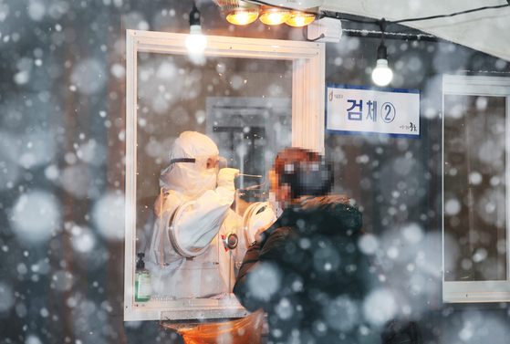 A man gets tested for the coronavirus Tuesday at Seoul Station Square amid heavy snow. [YONHAP]