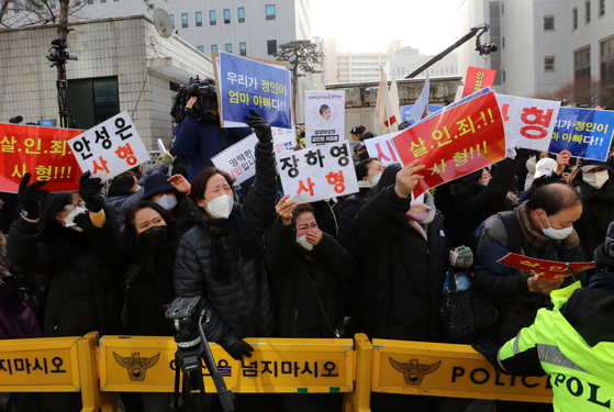 People hold up signs calling for a death sentence for the adoptive parents of a 16-month-old, who died after being brutally abused, at the Seoul Southern District Court on Wednesday, the first day of the trial of the adoptive parents. [NEWS1]