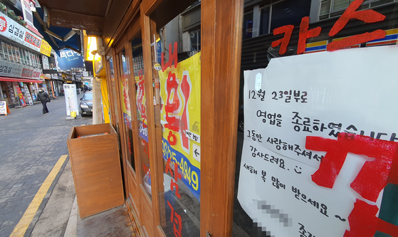 A sign announcing the close of business on Dec. 23, 2020, posted on an empty restaurant in downtown Seoul on Thursday. Many businesses either folded or are planning to do so due to the government's strict social distancing while the third wave of Covid-19 continues. [YONHAP]