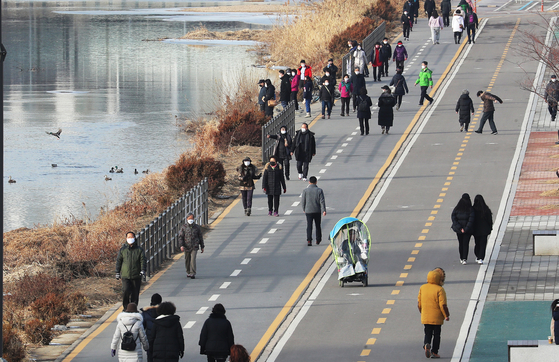 People stroll in a park in Jungnang District, northern Seoul, on Thursday as a cold wave abates. [YONHAP]