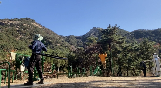 People making use of exercise equipment installed by Mount Bukhan. [KIM HONG-JOON]