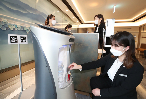 An employee at the five-star Daegu Marriott Hotel, which officially opened on Jan. 9, places water and shower products on a robot. According to KT, the newly opened hotel uses robots and runs on its artificial intelligence system. [KT]