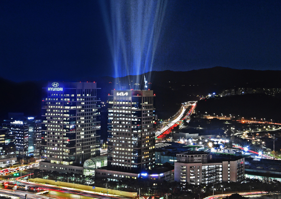 Kia's headquarters in southern Seoul, right, badged with a new logo. [KIA]