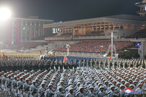 Thousands of North Korean soldiers march in unison at a military parade in Pyongyang on Thursday night, according to this state media photograph. [YONHAP]