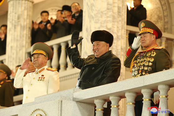 North Korean leader Kim Jong-un waves at troops marching at the military parade in Pyongyang on Thursday night, according to this state media photograph. [YONHAP]
