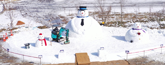 A worker build large snowmen in a park at Mount Naejang in Jeongeup, North Jeolla, Thursday. The Jeongeup city government said it hopes to send a message of hope to the nation fighting the coronavirus. [YONHAP]