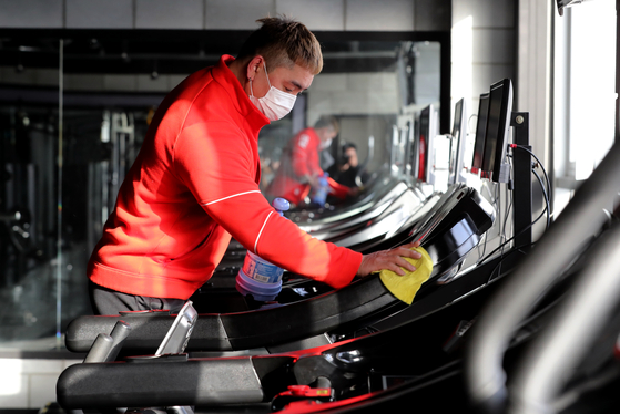 Kim Jang-hwan, owner of Synergy Gym in Incheon, cleans a treadmill on Thursday as he prepares for resuming business if health authorities lift restrictions. [NEWS1]