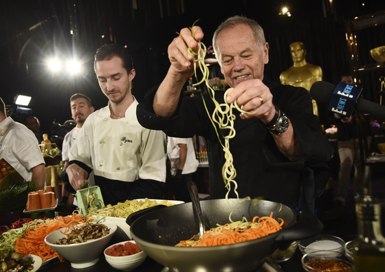 """Chef Wolfgang Puck, right, and his son Byron make a pasta dish at the Governors Ball Press Preview for the 92nd Academy Awards in Los Angeles on Jan. 31, 2020. A new four-part documentary series, """"The Event,"""" shows the intense planning and details that go into high-profile catering. [AP/YONHAP]"""