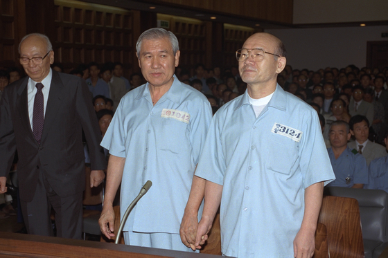 In this file photo, former Presidents Chun Doo Hwan, left, and Roh Tae-woo, stood in the courtroom in 1996 for their treason trial. [YONHAP]