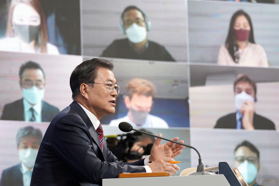President Moon Jae-in answers a question at a New Year's press conference at the Blue House on Monday. Twenty journalists attended in person and 100 via videoconference. [YONHAP]