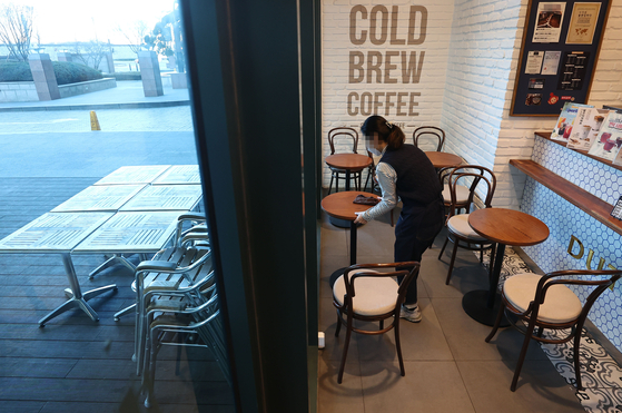 A worker at a coffee shop in downtown Seoul wipes tables Sunday, a day before customers will be allowed to eat and drink at cafes in Seoul, Incheon and Gyeonggi. [YONHAP]