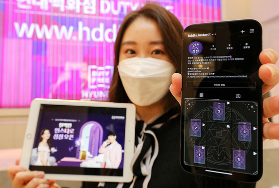 A model promotes a free tarot service at Hyundai Department Store Duty Free's Trade Center branch in Gangnam District, southern Seoul, on Monday. People who visit its official Instagram account and pick one of five tarot cards will be told their lucky number and items for the year. [HYUNDAI DEPARTMENT STORE]