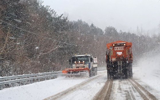 Snow plough trucks clear snow piled on the road in Yangyang County, Gangwon, on Monday after a heavy snowfall warning was issued in the area. [YONHAP]