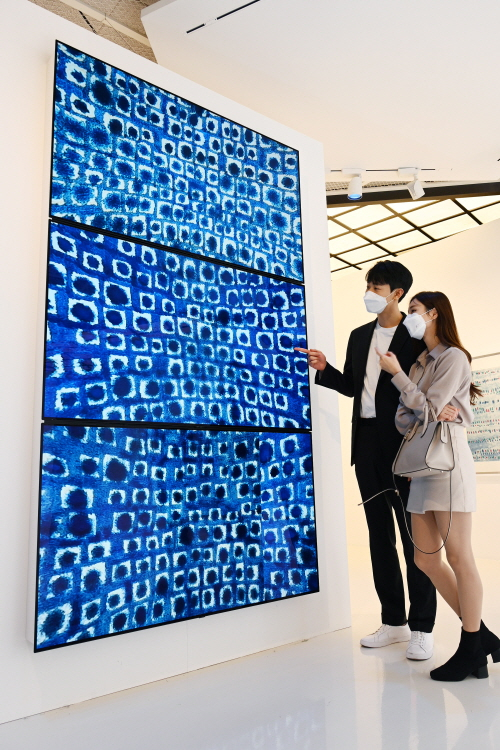 Models look at a work by the late Kim Whan-ki through LG Electronics' high-definition LED signage screens at Lotte Department Store's World Tower branch in southern Seoul on Monday. [LG ELECTRONICS]